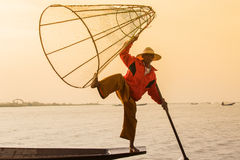 Burmese fisherman on bamboo boat catching fish in traditional way with handmade net. Inle lake, Myanmar (Burma) Stock Image
