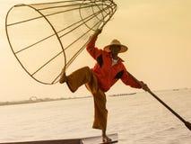 Burmese fisherman on bamboo boat catching fish in traditional way with handmade net. Inle lake, Myanmar , Burma Stock Images
