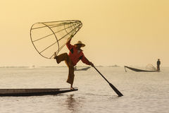 Burmese fisherman on bamboo boat catching fish in traditional way with handmade net. Inle lake, Myanmar, Burma Royalty Free Stock Photos