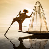 Burmese fisherman on bamboo boat catching fish in traditional way with handmade net. Inle lake, Myanmar , Burma Royalty Free Stock Photography