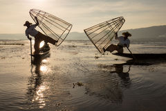 Burmese fisherman on bamboo boat catching fish in traditional way with handmade net. Inle lake, Myanmar, Burma Stock Images