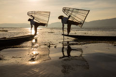 Burmese fisherman on bamboo boat catching fish in traditional way with handmade net. Inle lake, Myanmar, Burma Royalty Free Stock Photography