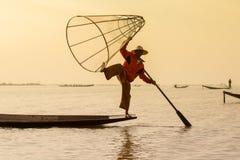 Burmese fisherman on bamboo boat catching fish in traditional way with handmade net. Inle lake, Myanmar, Burma Stock Image