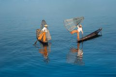 Burmese fisherman on bamboo boat catching fish. Myanmar. Burmese fisherman on bamboo boat catching fish in traditional way with handmade net. Inle lake, Myanmar stock photos