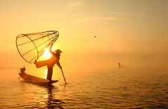Burmese fisherman on bamboo boat catching fish royalty free stock photos