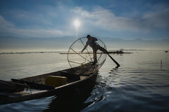 Burmese fisherman on bamboo boat catching fish in traditional way with handmade net. Royalty Free Stock Photography