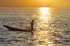 Burmese fisherman on boat catching fish in traditional way in Inle lake, Myanmar stock image
