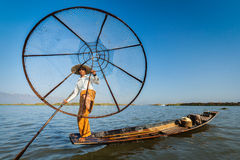 Burmese fisherman at Inle lake, Myanmar. Myanmar travel attraction landmark - Traditional Burmese fisherman with fishing net at Inle lake in Myanmar famous for stock image