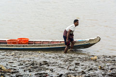 Burmese fisherman pulling the boat up on riverbank Royalty Free Stock Image