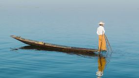 Burmese fisherman with a traditional trap on wooden boat. Inle lake, Myanmar stock footage