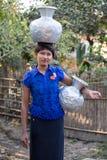 Burmese girl with big jugs with water. Mrauk U, Myanmar Royalty Free Stock Image
