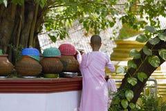Burmese girl monk getting fresh water from a terracotta pot at the Rangoon Buddhist Monastery, Yangon Rangoon Stock Photos