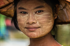 Burmese girl Myanmar. The Thanaka is a vegetable paste of soaked wood, from scented fragrance , made from the bark of palm Toddy Limonia very acid , with stock images