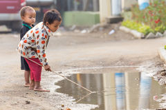 Burmese kids playing in Puddle. MANDALAY,MYANMAR,JANUARY 19, 2015: Kids playing with a stick in a puddle near the river Irrawaddy banks in Mandalay, Myanmar ( Stock Images