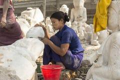 Burmese kvinna som snider en marmorBuddhastaty, Mandalay, Burma Arkivbild