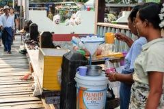 Burmese kvinnor göras ‹för â€, genom att hälla kallt vatten över den till salu isen Royaltyfria Bilder