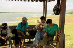 Burmese local playing Mandolin at a resting shelter at U-bein bridge Stock Photos