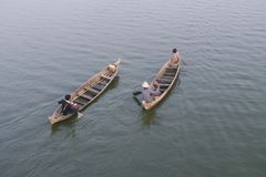Burmese locals rowing on traditional boats in Taungthaman lake, Burma royalty free stock images