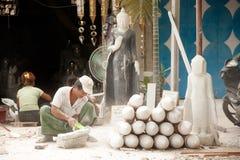 Burmese man carving a large marble Buddha statue. MANDALAY,MYANMAR - JULY 2 : Burmese man use tool carving a large marble Buddha statue, outdoors. Man is Stock Image