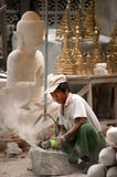 Burmese man carving a large marble Buddha statue. Stock Image