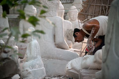 Burmese man carving a large marble Buddha statue. Royalty Free Stock Images