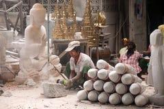 Burmese man carving a large marble Buddha statue. Stock Photos
