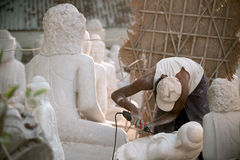Burmese man carving a large marble Buddha statue. Stock Photos