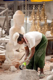 Burmese man carving a large marble Buddha statue. Royalty Free Stock Image