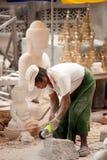 Burmese man carving a large marble Buddha statue. MANDALAY,MYANMAR - JULY 2 : Burmese man use tool carving a large marble Buddha statue, outdoors. Man is Royalty Free Stock Image