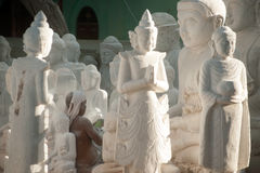 Burmese man carving a large marble Buddha statue. Royalty Free Stock Photography