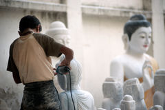 Burmese man carving a large marble Buddha statue. Stock Images