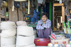 Burmese man selling at the market, Myanmar. Mrauk U, Myanmar - January 30, 2016. An unidentified Burmese man sells his wares at local market royalty free stock photo