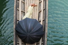 Burmese man sleeping in a boat covered with black umbrella on Inle lake, Myanmar. Ship, float, rest, wooden, drift, current, wetland, water-land, river, wave stock images