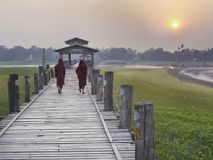 Burmese monks walking across the U Bein Bridge at sunset royalty free stock photography