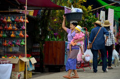 Burmese Mother hold the baby and carrying basin plastic on her h Royalty Free Stock Photography