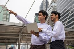 Burmese or Myanmar businessmen in city. Two Handsome Burmese or Myanmar businessmen with longyi traditional dress checking consturction project plan by laptop Royalty Free Stock Image
