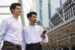 Burmese Myanmar businessmen in city. Two Handsome Burmese or Myanmar businessmen with longyi traditional dress look at business project in Bangkok Modern city royalty free stock photos