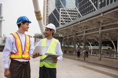 Burmese or Myanmar male engineers in city. Two Handsome Burmese or Myanmar engineer with longyi traditional dress dicsuss construction project plan with laptop royalty free stock images