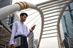 Burmese Myanmar man using smartphone in modern city. Handsome Burmese or Myanmar man with longyi traditional dress checking business project on smartphone and Royalty Free Stock Photos