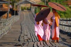 Burmese nuns. Alms were walking on a wooden bridge.Bridge of the Mon Sangklaburi near the Burmese border.Sam pra sob river.Sanbkhlaburi Kanchanaburi Thailand royalty free stock photos