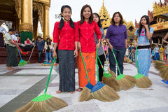 Burmese people participate in a ceremony with brooms at the Shwedagon Pagoda. Yangon, Myanmar Stock Photo