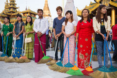 Burmese people participate in a ceremony with brooms at the Shwedagon Pagoda. Yangon, Myanmar Royalty Free Stock Photos