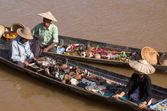 Burmese people on small long wooden boat selling souvenirs, trinkets and bijouterieat the floating market on Inle lake, Myanmar, B Stock Photography