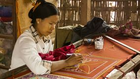 Burmese tapestry masters work with kalaga. It is a heavily embroidered applique tapestry made of stock footage