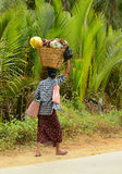 Burmese woman is carrying a bag on her head Stock Photography