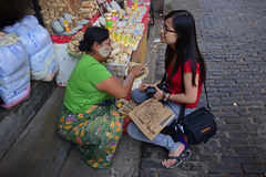 Burmese woman helping to apply freshly made Thanaka paste to a young foreign tourist girl Royalty Free Stock Photo