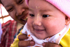 Burmese woman with her baby in December 14, 2012 in Kyaikto, Myanmar. Stock Photos