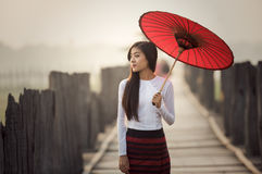 Burmese woman holding traditional. Red umbrella and walking on U Bein Bridge stock photo