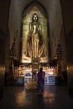 Burmese woman praying in front of huge golden buddha Stock Photo