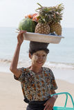 Burmese woman selling fresh fruits at the shoreline to tourists in Ngapali beach. Myanmar Stock Photos